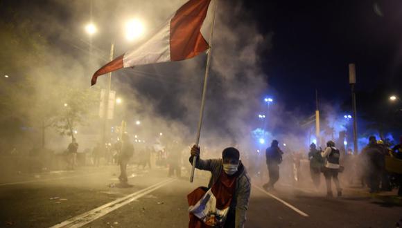 Un manifestante sostiene una bandera del Perú mientras la policía arroja bombas lacrimógenas en la avenida Abancay. (Foto de ERNESTO BENAVIDES / AFP).