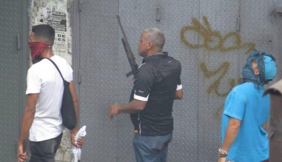 Un colectivo camina llevando un arma de largo alcance durante una protesta en la avenida Fuerzas Armadas, en el centro de Caracas.