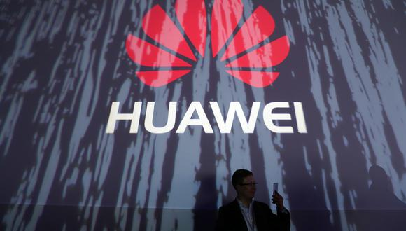 An attendee holds a smartphone in front of a Huawei Technologies Co. logo at the launch event of their P9 smartphone in London, U.K., on Wednesday, April 6, 2016. Huawei's profit surged 33 percent in 2015 after China's largest maker of telecommunications gear grabbed market share with premium smartphones and mobile carriers expanded their high-speed networks globally. Photographer: Chris Ratcliffe/Bloomberg