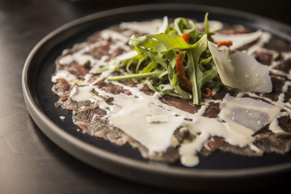 Carpaccio de lomo fino curado por 8 horas. Viene con arúgula, tomates confitados y láminas de Grana Padano.