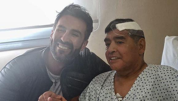 Esta fotografía tomada el 11 de noviembre de 2020 muestra a la leyenda del fútbol argentino Diego Maradona estrechando la mano de su médico Leopoldo Luque. (AFP).