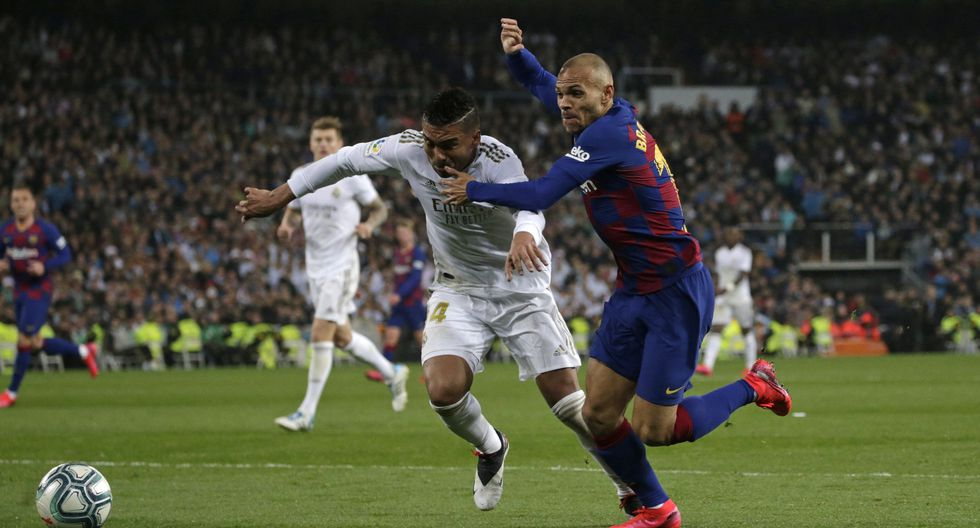 Barcelona's Martin Braithwaite, right, tries to get past Real Madrid's Casemiro during the Spanish La Liga soccer match between Real Madrid and Barcelona at the Santiago Bernabeu stadium in Madrid, Spain, Sunday, March 1, 2020. (AP Photo/Andrea Comas)