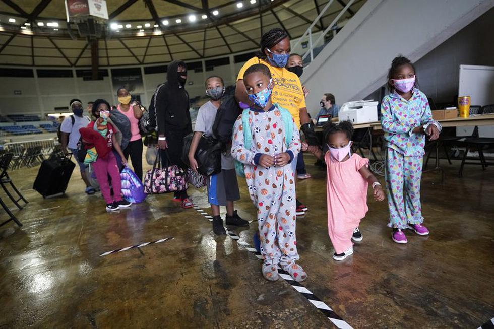 Victoria Nelson y sus hijos Autum Nelson, 2, Shawn Nelson, 7, y Asia Nelson, 6, hacen fila para abordar un autobús para evacuar Lake Charles, Louisiana, el miércoles 26 de agosto de 2020, antes de la llegada del huracán Laura. (Foto AP / Gerald Herbert).