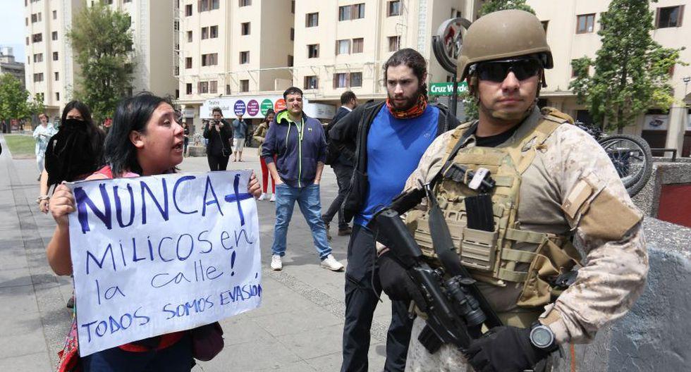 Una mujer se manifiesta contra la presencia de militares en zonas urbanas este sábado en inmediaciones de las estaciones del metro. (Foto: EFE)