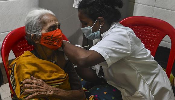 Personal médico inocula a una anciana con una dosis de Covishield, vacuna contra el coronavirus Covid-19 de AstraZeneca-Oxford, en Mumbai, India. (Foto de INDRANIL MUKHERJEE / AFP).
