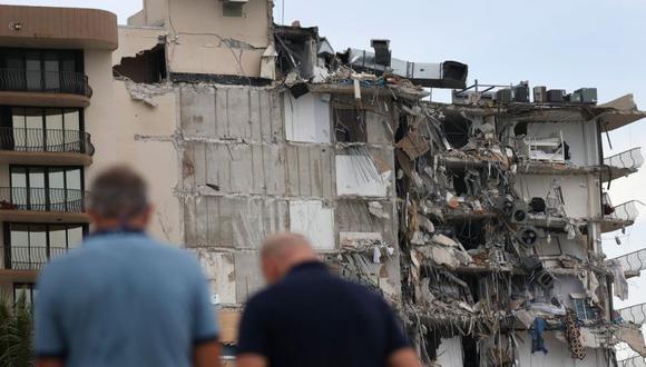 La gente mira una parte del edificio de condominios Champlain Towers South de 12 pisos que se derrumbó parcialmente en Surfside, Florida. (Foto: Joe Raedle / Getty Images / AFP).