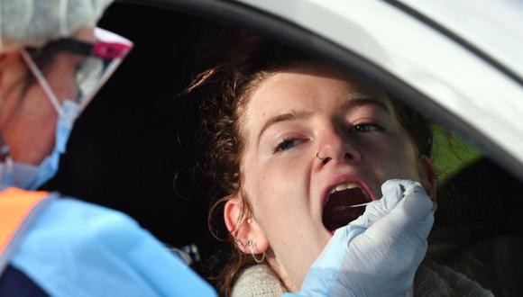 Personal sanitario toma un hisopado a una mujer en una estación de prueba de coronavirus COVID-19 en Picton, a unos 80 kilómetros al suroeste de Sydney, Australia. (Foto: SAEED KHAN / AFP).