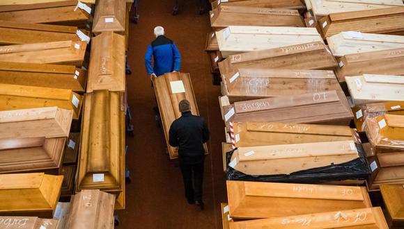 """Los empleados trabajan entre ataúdes, algunos marcados con """"riesgo de infección"""", mientras que otros tienen """"corona"""" garabateada con tiza, en la sala de duelo del crematorio en Meissen, en el este de Alemania. (Foto de JENS SCHLUETER / AFP)."""