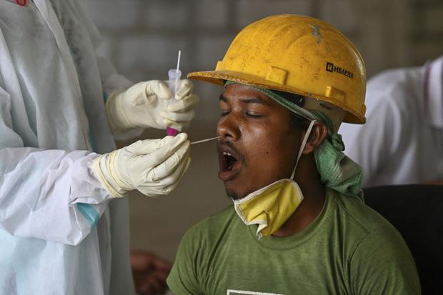 A health worker takes a swab sample from a person for a Govt-19 corona virus test at a construction site in New Delhi, India.  (Photo by Prakash Singh / AFP).