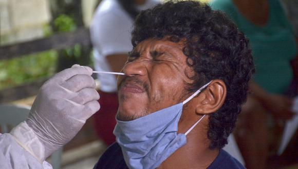 Un trabajador de salud recolecta una muestra de hisopo de un residente para realizar una prueba de COVID-19 en Bela Vista do Jaraqui, Manaos, Brasil. (Foto de MARCIO JAMES / AFP).