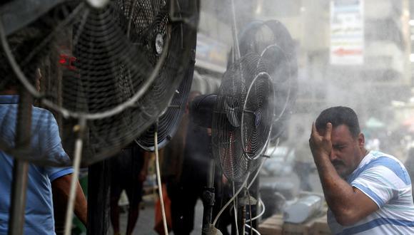 Un hombre recibe aire de ventiladores que rocían aire mezclado con vapor de agua desplegado por donantes para enfriar a los peatones a lo largo de una calle en la capital de Irak, Bagdad, el 30 de junio de 2021 en medio de una fuerte ola de calor. (Foto: AHMAD AL-RUBAYE / AFP)