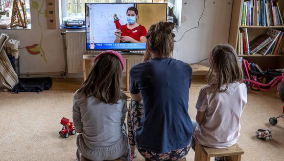 """""""En medio de esta pandemia, los padres necesitamos hacer muchas cosas que antes no hacíamos, [como] acompañar a los niños como asistentes de docencia en su ahora colegio virtual"""". (Foto referencial: AFP)."""