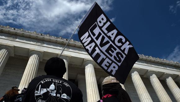 """Foto referencial. Una persona sostiene una bandera de Black Lives Matter durante la protesta """"Marcha de compromiso: quítese la rodilla del cuello"""" contra el racismo y la brutalidad policial, en el Lincoln Memorial el 28 de agosto de 2020, en Washington DC. (Olivier DOULIERY / POOL / AFP)."""