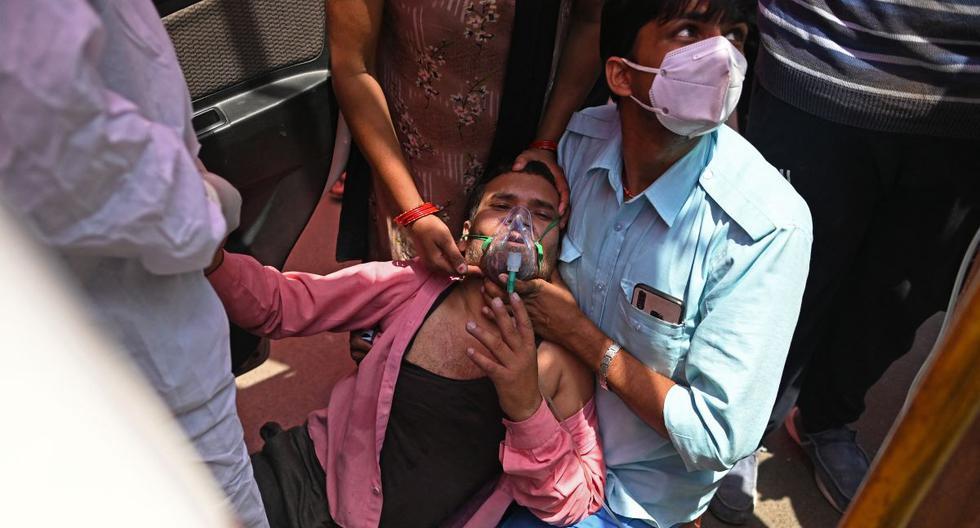 La India superó este miércoles las 200.000 muertes por coronavirus. En la imagen, un paciente respira con la ayuda de oxígeno al costado de la carretera en medio de la pandemia de coronavirus COVID-19 en Ghaziabad. (Foto de Sajjad HUSSAIN / AFP).