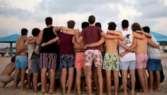 Jóvenes con trajes de baño se acurrucan para tomar una foto mientras visitan la playa de Zikim, en medio del brote de la enfermedad por coronavirus, en el sur de Israel. 21 de julio de 2020. (REUTERS/Amir Cohen).