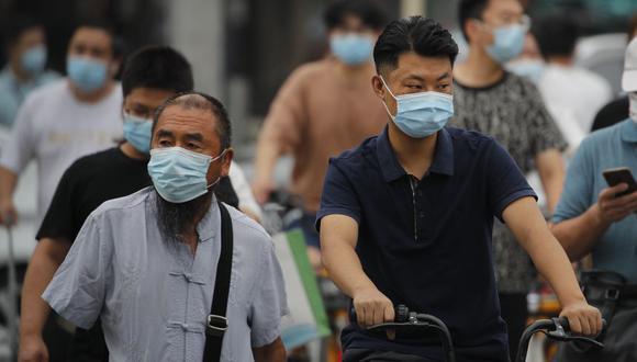 La mayoría de las personas todavía usan mascarillas a pesar de que el brote de coronavirus ha estado bajo control en la capital china. (Foto: AP / Andy Wong)