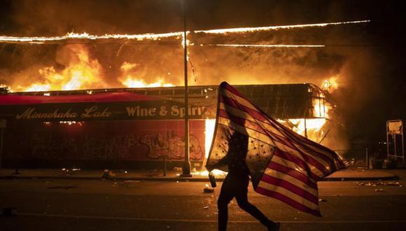 Un manifestante lleva una bandera estadounidense invertida frente a un edificio en llamas en Minneapolis. (Foto: AP/Julio Cortez).