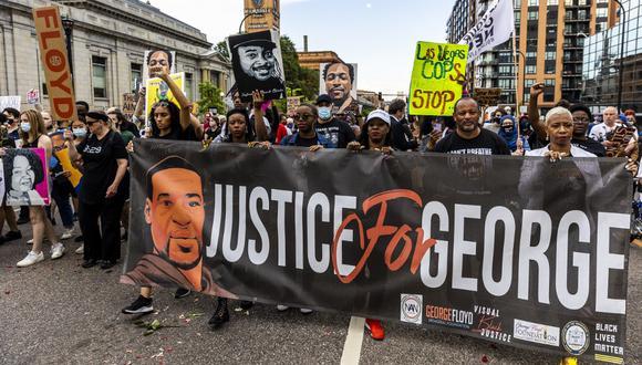 La gente sostiene carteles y una pancarta mientras marchan durante un evento en memoria de George Floyd en Minneapolis, Minnesota, el último domingo. (Kerem Yucel / AFP)