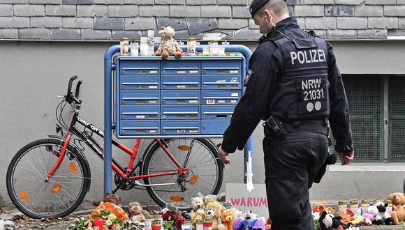 Un policía pasa frente a velas y osos de peluche en la entrada de una casa en donde cinco niños fueron encontrados muertos en Solingen, Alemania, el viernes 4 de septiembre de 2020.