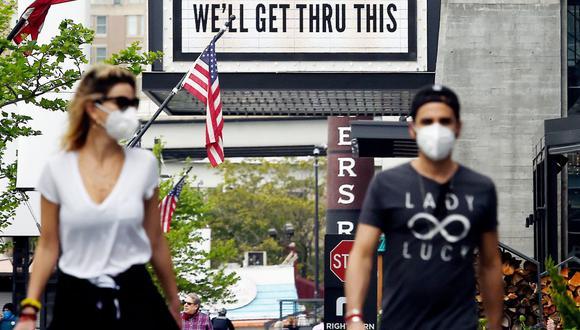 Imagen referencial. Los peatones pasan junto a un cartel frente a The Anthem, un popular lugar de música en vivo, el 29 de abril de 2020, en Washington, DC. (Olivier DOULIERY / AFP).