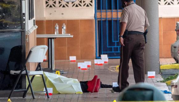 Un oficial de policía revisa el cuerpo de una víctima de un tiroteo, en la entrada del salón de banquetes Billiards en Miami Gardens, Florida, Estados Unidos. (EFE / EPA / CRISTOBAL HERRERA-ULASHKEVICH).