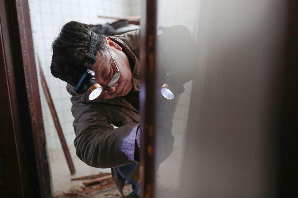 Ma Jiale pule un montante de puerta de madera en uno de los inmuebles del barrio histórico de la ciudad. (Foto: AFP)
