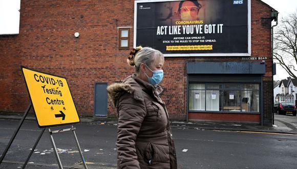 Una mujer pasa junto a un cartel de información sobre el coronavirus en el Walsall Arena & Arts Center, en Inglaterra, el 4 de febrero de 2021. (Foto de Oli SCARFF / AFP).