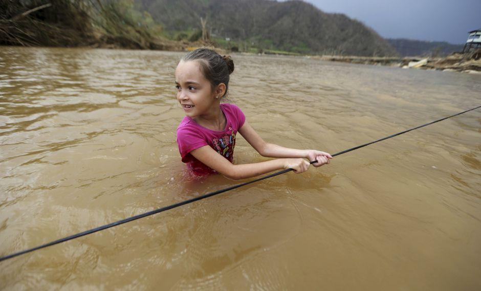 Puerto Rico. Muchos lugares siguen inundados pese a que ya pasó una semana del huracán. En la imagen, una niña en la ciudad de Morovis. (AP)
