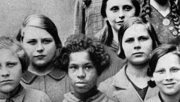 """Esta foto fue usada en conferencias sobre genética de la Academia Alemana para la Raza y la Salud en 1936. Título original: """"niña mulata de una mujer alemana y un negro de las tropas de la Renania francesa, entre sus compañeros de clase alemanes""""."""