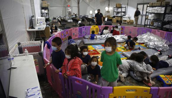 Niños migrantes no acompañados, de 3 a 9 años, ven televisión dentro de un corralito en el centro de detención del Departamento de Seguridad Nacional de Donna, en Texas, Estados Unidos. (Foto de Dario Lopez-Mills / POOL / AFP).