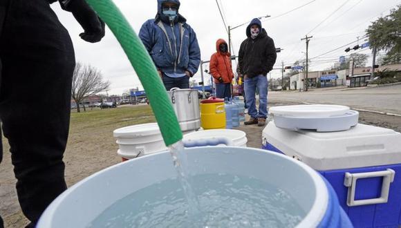 Una persona llena un barril de agua mientras otros esperan en temperaturas bajo cero en un parque en Houston, Texas. (AP Foto/David J. Phillip).