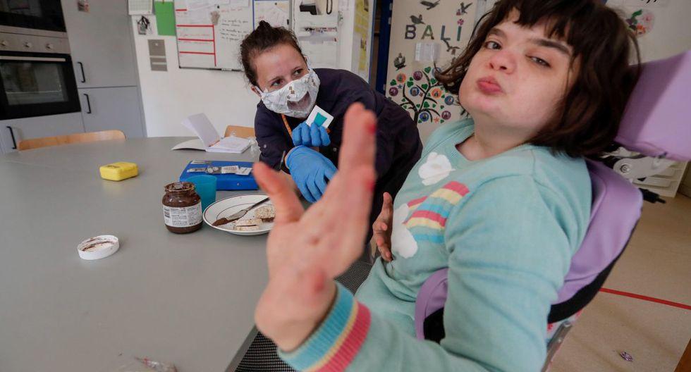 Una terapista de lenguaje cuida de Aglae, una joven de 18 años considerada el primer paciente belga en ser diagnosticada con el Síndrome de Charge, una condición que engloba anomalías oculares, defectos en el funcionamiento del corazón, anomalía nasal, dificultad respiratoria, retraso en el desarrollo físico y mental, desarrollo genital incompleto y malformación en el oído acompañado de pérdida auditiva. Aglae se atiende en IRSA, un instituto especializado para personas sordas y ciegas en Bruselas que tras la crisis del coronavirus viene tomando estrictas medidas de higiene y distanciamiento social. (EFE / EPA / STEPHANIE LECOCQ)
