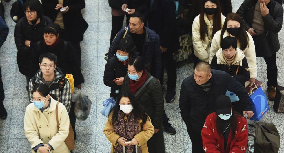 Los viajeros usan máscaras mientras hacen fila para un tren en la estación de Hangzhou. (AP).