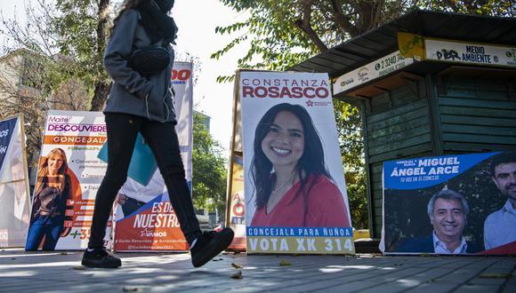 Una mujer pasa por delante de la propaganda electoral en Santiago (Chile), el 12 de mayo de 2021. (MARTIN BERNETTI / AFP).