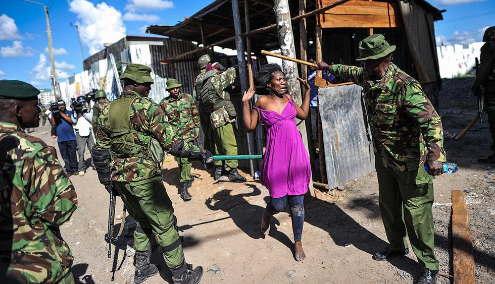 TOPSHOT - A woman puts her hands up as anti-riot policemen flush out opposition supporters, who had taken cover in a shack to escape teargas, during demonstrations in the Umoja subururb of Nairobi on November 28, 2017, following a denial of permission by police to the National Super Alliance (NASA) leader to hold a rally concurrently to the inauguration of the country's new president. President Uhuru Kenyatta vowed to be the leader of all Kenyans and work to unite the country after a bruising and drawn out election process that ended with his swearing-in. / AFP / TONY KARUMBA