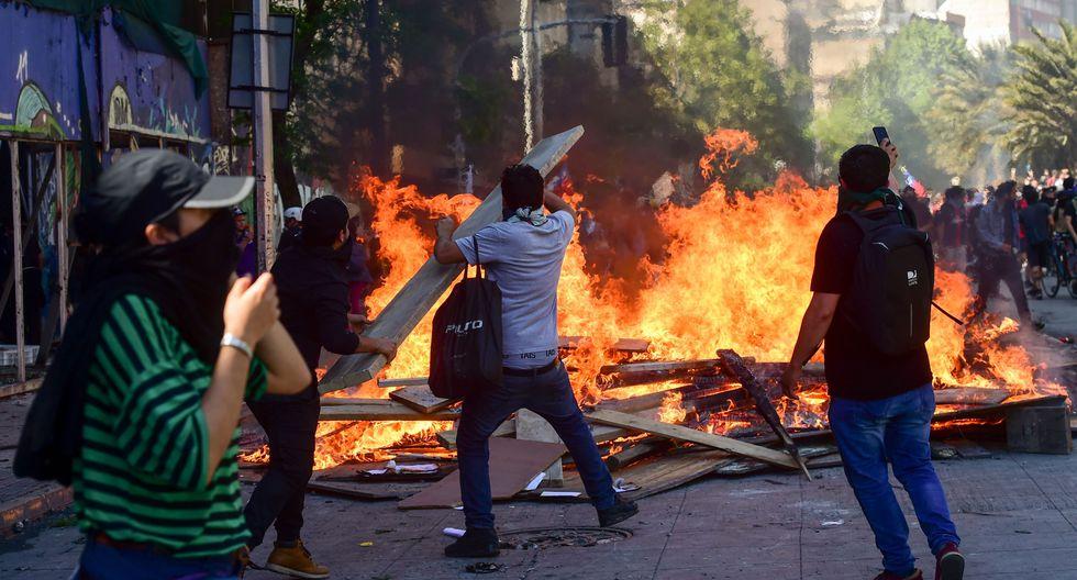 Un grupo de manifestantes prende fuego a una barricada durante una protesta en Santiago. (AFP / Martin BERNETTI).