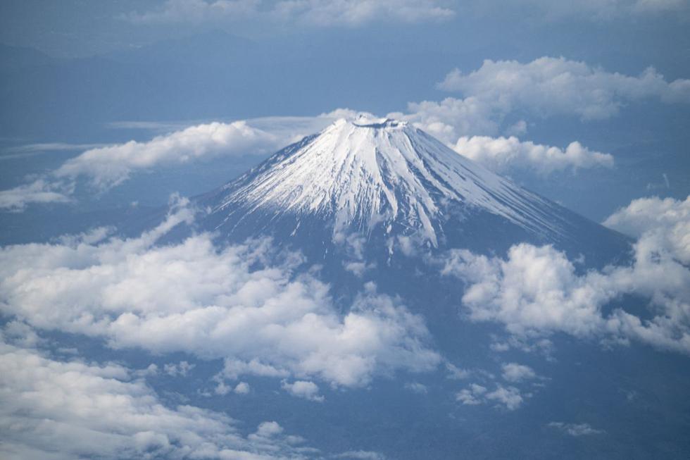 El monte Fuji, la montaña más alta de Japón con 3.776 metros es considerado Patrimonio de la Humanidad. La imagen muestra una vista desde la ventana de un avión de pasajeros en ruta a Kagoshima el 14 de mayo de 2021.  (Foto: AFP)