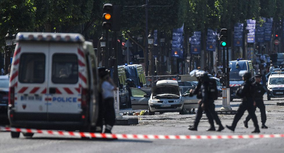 Policemen are at work near the wreckage of a car (C), on June 19, 2017 on the Champs-Elysees avenue in Paris, after it crashed into a police van before bursting into flames, with the driver being armed, probe sources said.   / AFP / ALAIN JOCARD