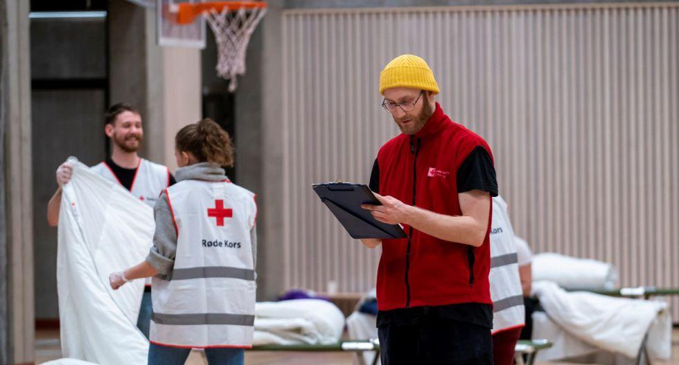 En la imagen se muestran a un grupo de voluntarios preparando camas en el gimnasio de la escuela cerrada de Uranienborg, donde la Cruz Roja ha establecido un refugio temporal para personas sin hogar debido a la nueva pandemia de coronavirus, en Oslo. (Heiko Junge / NTB Scanpix / AFP)