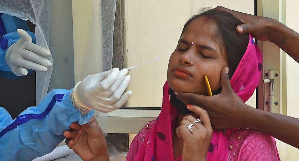 Un funcionario de salud recoge una muestra de hisopo de una mujer para analizar el coronavirus COVID-19, en un centro de pruebas temporal en Nueva Delhi, en la India. La imagen es del último 28 de julio. (Foto: AFP / Money Sharma)