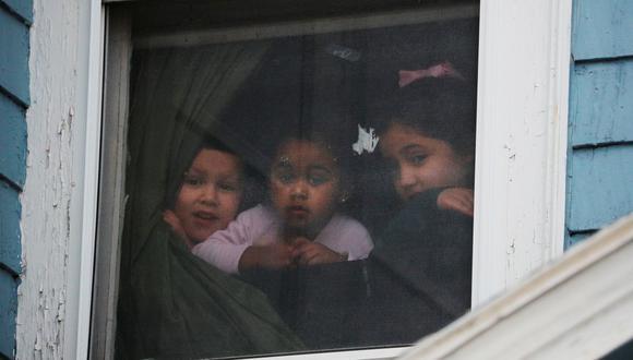 Un grupo de niños miran por una ventana durante la cuarentena por el brote de coronavirus (COVID-19) en Chelsea, Massachusetts, Estados Unidos. (Foto: Reuters)