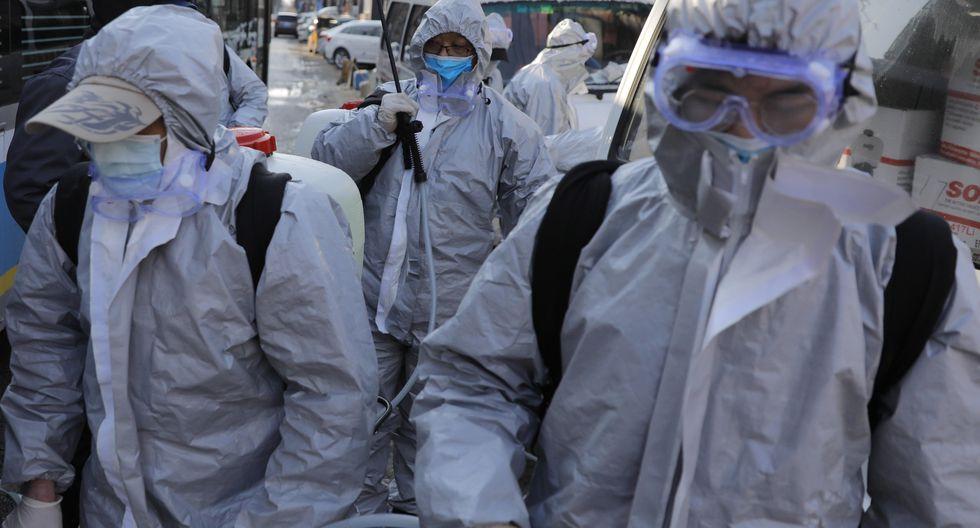 Trabajadores que usan trajes protectores se reúnen después de desinfectar un área residencial en Beijing, China, para prevenir la expansión del coronavirus. (EFE / EPA / WU HONG).