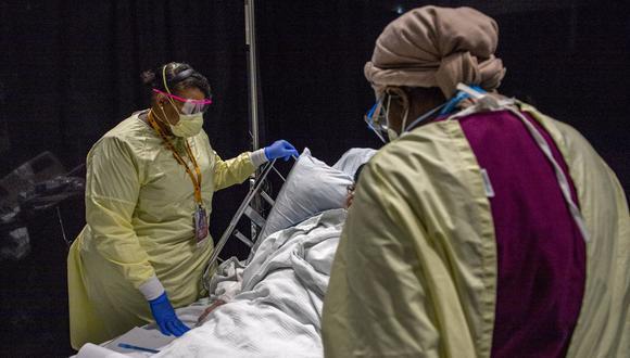 Personal sanitario atiende y consuela a un paciente de coronavirus Covid-19 en el Hospital de campo UMASS Memorial DCU Center en Worcester, Massachusetts, Estados Unidos, país golpeado por la variante Delta. (Foto de Joseph Prezioso / AFP).