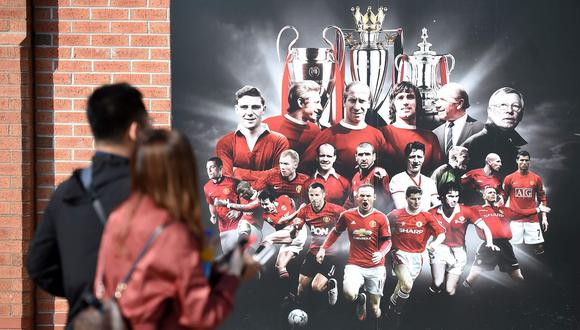 A visitor walks past a billboard featuring football greats, including legendary football manager Sir Alex Ferguson, (top-R), outside the Manchester United Museum at Old Trafford football stadium, Manchester on May 6, 2018. Messages of support continued to pour in as legendary football manager Sir Alex Ferguson fought for his life on May 6, 2018, following emergency surgery for a brain haemorrhage. - RESTRICTED TO EDITORIAL USE. No use with unauthorized audio, video, data, fixture lists, club/league logos or 'live' services. Online in-match use limited to 75 images, no video emulation. No use in betting, games or single club/league/player publications.   / AFP / Paul ELLIS                        / RESTRICTED TO EDITORIAL USE. No use with unauthorized audio, video, data, fixture lists, club/league logos or 'live' services. Online in-match use limited to 75 images, no video emulation. No use in betting, games or single club/league/player publications.