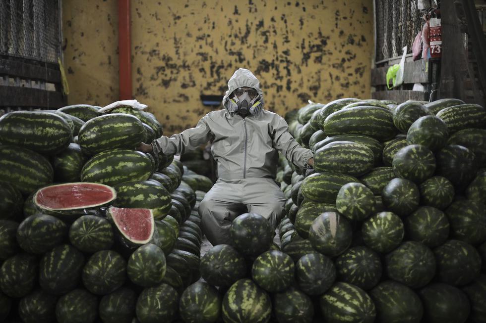 Un comerciante del Mercado de Frutas utiliza un mameluco para prevenir la propagación del Covid-19. Foto: Joel Alonzo/ @photo.gec