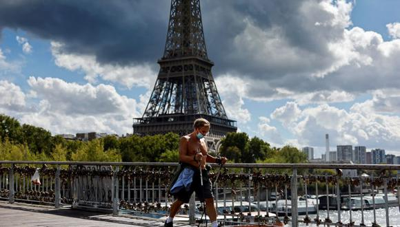 Un hombre que usa mascarilla protectora pasa por delante de la Torre Eiffel en París el 28 de agosto de 2020. (Foto de Thomas COEX / AFP).