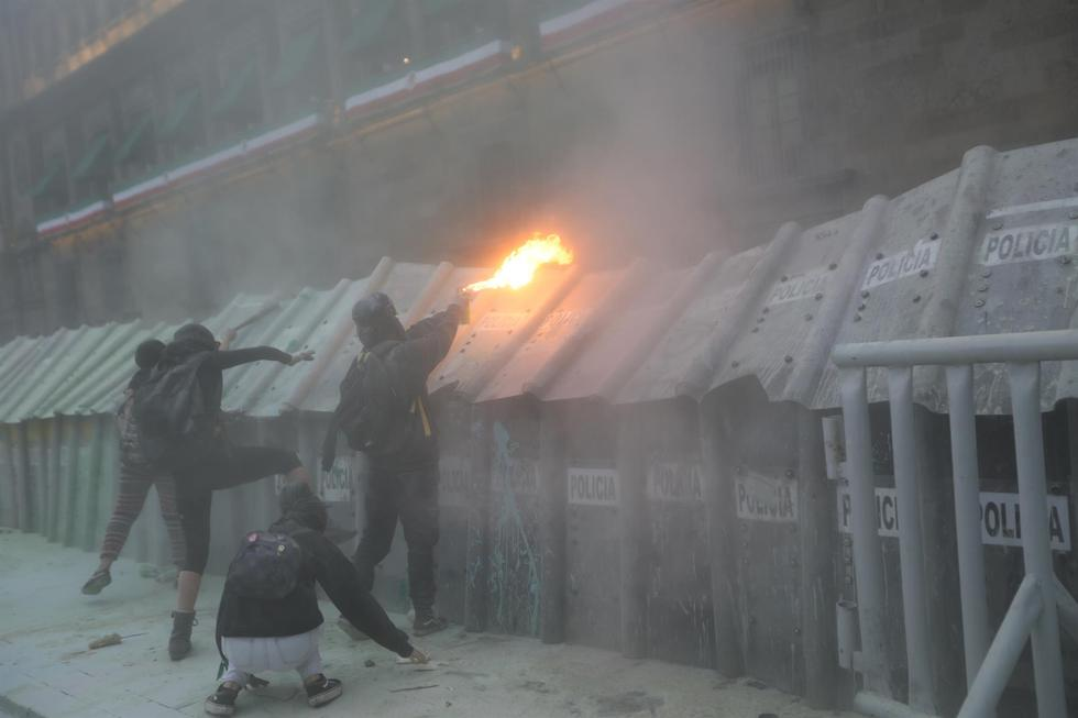 Colectivos feministas se manifiestan durante una protesta en la capital de México e intentan quemar a policías que resguardan el Palacio Nacional. (EFE/Sáshenka Gutiérrez).