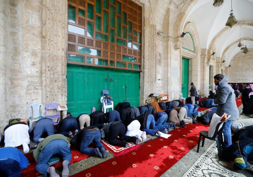Los musulmanes palestinos se reúnen para realizar sus oraciones del viernes frente a las puertas cerradas de la mezquita Al-Aqsa en la Ciudad Vieja de Jerusalén. (Foto: AFP)