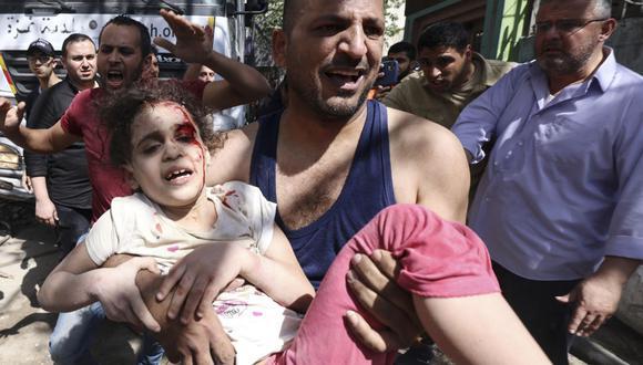 Los palestinos evacuan a una niña herida de los escombros de un edificio destruido en el distrito residencial Rimal, en Gaza, luego del bombardeo masivo de Israel. (Foto de MAHMUD HAMS / AFP).
