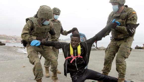 Miembros del Ejército de Tierra de España ayudan a un inmigrante que ha logrado cruzar uno de los espigones fronterizos de Ceuta este martes. (EFE/Reduan).